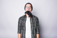 Young guy with eyeglasses holding joystick Royalty Free Stock Photography