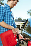 Young guy filling his car. Young guy fills his car by using canister Royalty Free Stock Photography