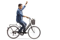 Young guy with a football riding a bike and gesturing happiness Stock Photo