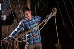 Young guy freed from captivity and selecting from ropes. Escape the room game concept royalty free stock photos