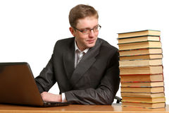 Young guy  get information from a laptop or paper books Stock Photography