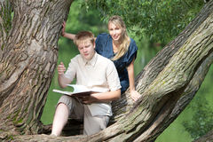 Young guy and girl with books on nature Stock Photos