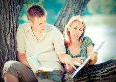 Young guy and girl with books on the nature near lake,with a retro effect Stock Photography
