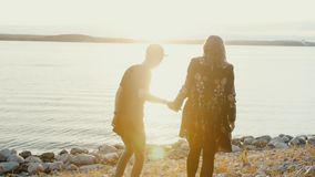 Young guy and girl couple in love go to the water`s edge on rocky beach stock footage