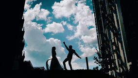 A young guy and a girl dancing against a beautiful sky. stunning clouds in the background. two lovers spinning in the dance. Beautiful dance of love stock video footage
