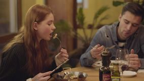 Attractive young guy and girl on a date in an expensive restaurant. Friends eat delicious gourmet meals for dinner. stock video