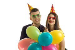 Young guy with a girl, holding near the eye paper glasses happily laughing and carrying balloons Stock Photos