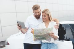 A young guy and a girl are looking at a map of highways. They prepare to travel and choose the road. They stand near their white electric vehicle stock images