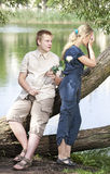 Young guy and girl on the nature near lake, reconciliation after quarrel Royalty Free Stock Photo