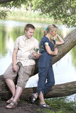 Young guy and girl on the nature near lake, reconciliation after quarrel Royalty Free Stock Photos