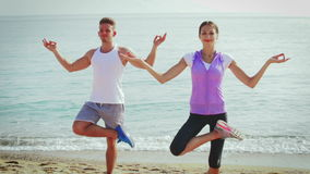 Young guy and girl practising yoga poses stock video