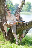 Two teenagers read books outdoors in a sunny day Stock Image