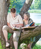 Two teenagers read books outdoors Royalty Free Stock Image
