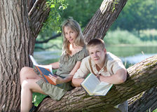 The young loving couple reads books on the bank of the lake Stock Image