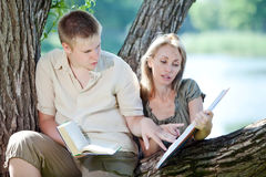 Young guy and girl prepare for lessons in park Stock Image