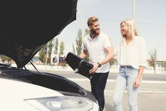 A young guy and a girl put luggage in the trunk of their electric car. It is located in front of the machine. It`s a suitcase Stock Images