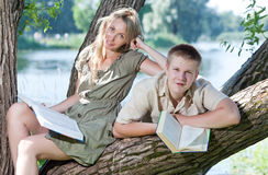 The young guy and the girl read books outdoors Stock Images