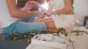 Young guy and girl sitting on the couch, laughing, flirting and having fun with a lights Royalty Free Stock Photos