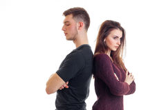 Young guy and girl stand backs to each other with folded hands. On white background royalty free stock image