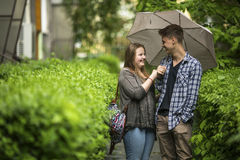 Young guy and girl talking under an umbrella. Love. Stock Image