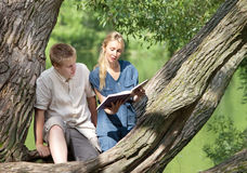 Young guy and girl with textbooks on bank of lake Stock Photos