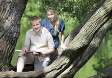 Young guy and the girl with textbooks on the bank of lake Stock Photos