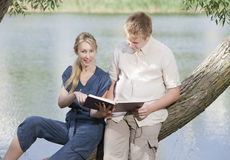 Young guy and the girl with textbooks on the bank of lake Royalty Free Stock Image