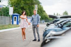 A young couple is choosing a used car. Used car theme. A young guy with a girl walks in the parking lot and chooses a car royalty free stock photos
