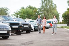 A young couple is choosing a used car. Used car theme. A young guy with a girl walks in the parking lot and chooses a car royalty free stock images
