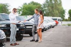A young couple is choosing a used car. Used car theme. A young guy with a girl walks in the parking lot and chooses a car royalty free stock image