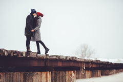 Young guy and girl in winter wear, embrace and enjoy the scenery of winter. Stock Image