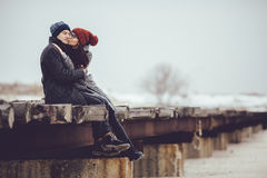 Young guy and girl in winter wear, embrace and enjoy the scenery of winter. Stock Photo