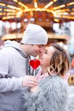 Happy young couple in love with red heart candy in hands nose kissing. Christmas lights background royalty free stock image