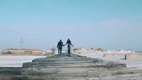 Young guy and girl in winter wear, walking on the bridge of planks, a beautiful winter sunny day. stock video