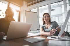 Young guy and girl working together. Low angle of coworkers sitting at the office desk and debating. Enjoyed women showing documentation and men looking at Royalty Free Stock Photos