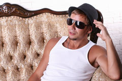 Young guy with glasses and hat sits on couch Stock Photography