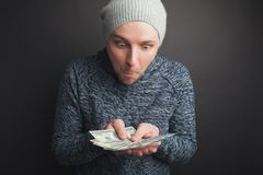 A young guy in a gray cap and a beard, holding a stack of money and stares at it on a black background. Freelancer admire its its royalty free stock photo