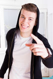 Young guy with great smile in active sportswear hood pointing Royalty Free Stock Photography