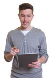 Young guy in a grey shirt working with tablet computer Royalty Free Stock Photography