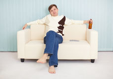Young guy has rest on a sofa with beer and TV Royalty Free Stock Photo