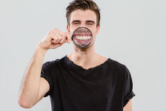 Young guy having fun with magnifying glass Royalty Free Stock Images