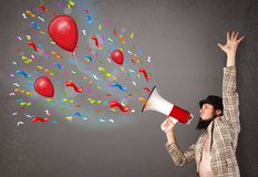 Young guy having fun, shouting into megaphone with balloons Stock Images