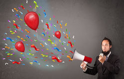 Young guy having fun, shouting into megaphone with balloons Royalty Free Stock Photos