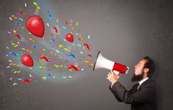 Young guy having fun, shouting into megaphone with balloons Stock Photos