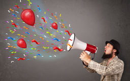 Young guy having fun, shouting into megaphone with balloons Royalty Free Stock Photo