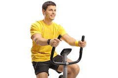 Young guy with headphones exercising on a stationary bike. Isolated on white background Stock Photo
