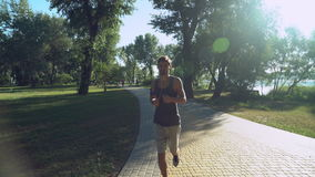 A young guy with headphones running back in the park, where walking and running other people. stock video footage