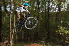 A young guy in a helmet flies on a bicycle after jumping from a kicker Royalty Free Stock Photography