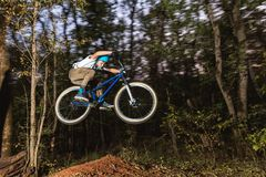 A young guy in a helmet flies on a bicycle after jumping from a kicker Stock Photos