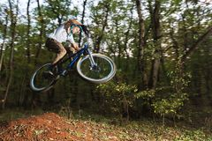 A young guy in a helmet flies on a bicycle after jumping from a kicker Stock Photo